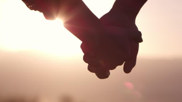 Hand holding, sunset
